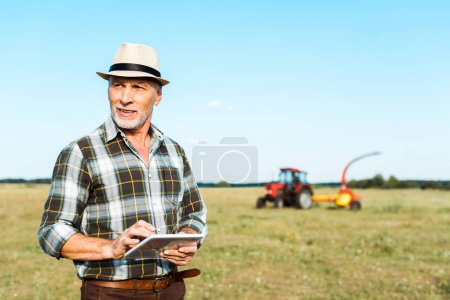 Photo for Cheerful self-employed farmer in straw hat using digital tablet in field - Royalty Free Image