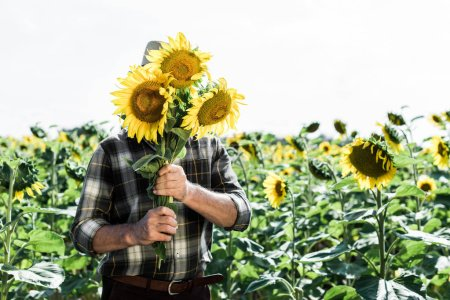 farmer covering face while holding sunflowers near field