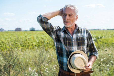 Photo for Smiling senior farmer holding straw hat in field - Royalty Free Image