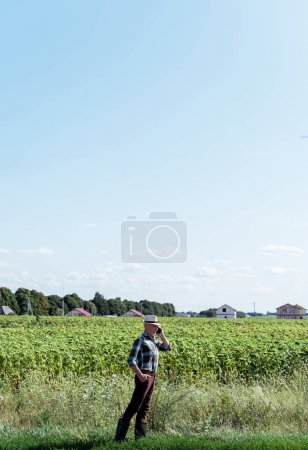 Photo for Self-employed farmer talking on smartphone while standing with hand on hip - Royalty Free Image
