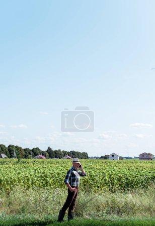 agriculteur indépendant parler sur smartphone tout en se tenant avec la main sur la hanche