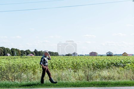 Photo for Bearded self-employed farmer talking on smartphone while walking in field - Royalty Free Image