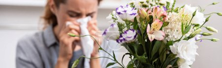 panoramic shot of bouquet of flowers near woman with pollen allergy sneezing in tissue