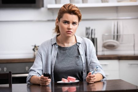 Photo for Sad woman with sweet allergy sitting near pink dessert and holding glucose monitor - Royalty Free Image