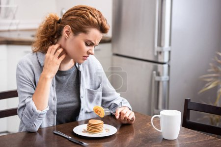 Photo for Attractive woman with allergy scratching neck while holding fork with pancake - Royalty Free Image