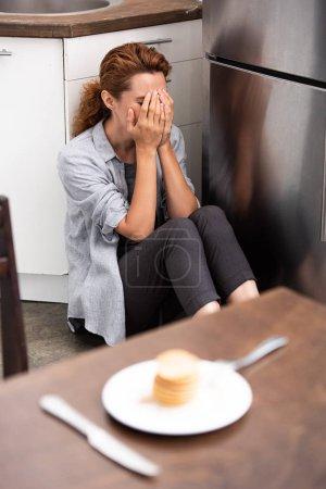 enfoque selectivo de la mujer sentada en el suelo y cubriendo la cara