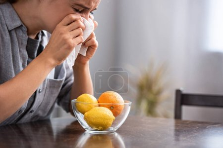 Photo for Woman with closed eyes sneezing in tissue near orange and lemons in bowl - Royalty Free Image