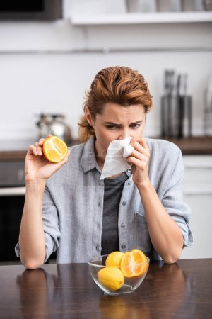 Photo for Woman with runny nose sneezing in tissue and holding half of tasty orange - Royalty Free Image