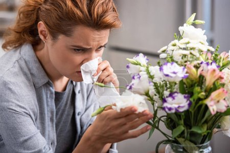 selective focus of woman with pollen allergy holding tissue and touching flowers