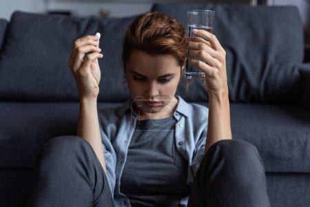 Photo pour Femme bouleversée et malade tenant la pilule et le verre de l'eau - image libre de droit