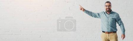 Photo pour Tir panoramique de l'homme d'affaires beau et souriant dans la chemise pointant avec le doigt - image libre de droit