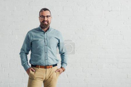 Photo pour Homme d'affaires beau et souriant en chemise avec les mains dans les poches - image libre de droit