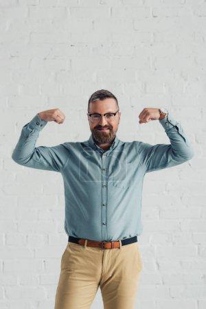 Photo pour Homme d'affaires beau et souriant dans la chemise affichant le geste dans le bureau - image libre de droit