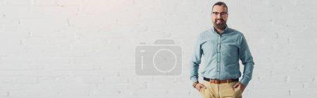 Photo pour Tir panoramique de l'homme d'affaires beau et souriant dans la chemise avec des mains dans des poches - image libre de droit