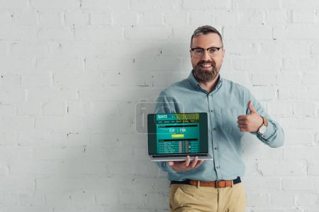 Photo for Handsome and smiling businessman showing thumb up and holding laptop with sports bet website - Royalty Free Image