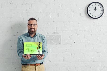 Photo pour Homme d'affaires beau et souriant retenant l'ordinateur portatif avec le meilleur site Web d'achats - image libre de droit