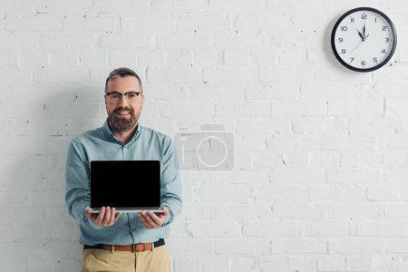 Photo pour Homme d'affaires beau et souriant tenant ordinateur portable avec espace de copie - image libre de droit