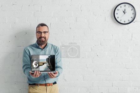 guapo y sonriente hombre de negocios sosteniendo portátil con sitio web de reserva