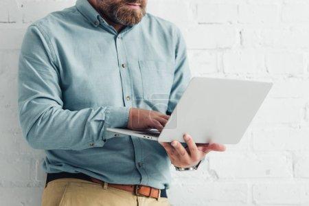 Photo pour Vue recadrée de l'homme d'affaires dans l'ordinateur portatif de fixation de chemise dans le bureau - image libre de droit