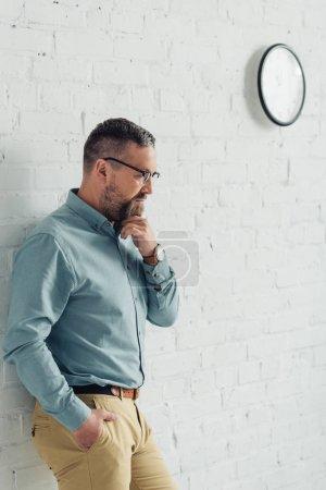 hombre de negocios pensativo en camisa y gafas mirando hacia otro lado en la oficina