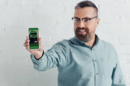 Photo for Selective focus of handsome businessman holding smartphone with booking website - Royalty Free Image