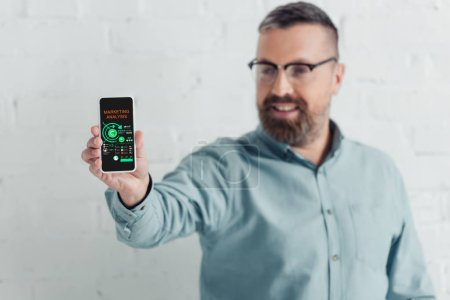 Photo for Selective focus of handsome businessman holding smartphone with charts and graphs website - Royalty Free Image