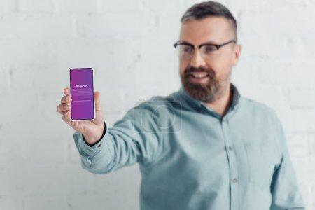Photo pour Kiev, Ukraine - 27 août 2019: focus sélectif d'un bel homme d'affaires tenant smartphone avec une application instagram - image libre de droit
