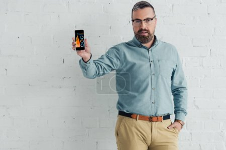handsome businessman with hand in pocket holding smartphone with charts and graphs website