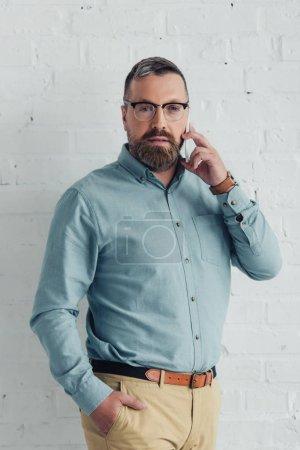 Photo pour Homme d'affaires beau avec la main dans la poche parlant sur le smartphone - image libre de droit