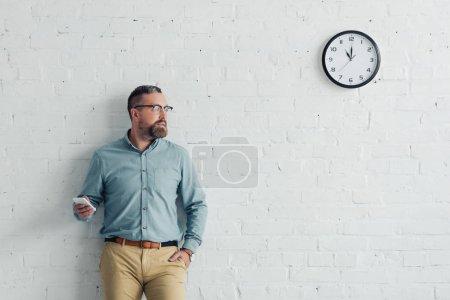 Photo pour Homme d'affaires beau avec la main dans le smartphone de fixation de poche dans le bureau - image libre de droit