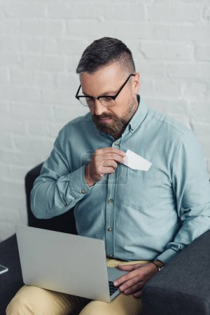 Photo for Handsome businessman in shirt and glasses holding blank card and laptop - Royalty Free Image