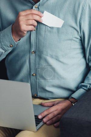 Photo pour Vue recadrée de l'homme d'affaires dans la chemise retenant la carte blanche et l'ordinateur portatif - image libre de droit