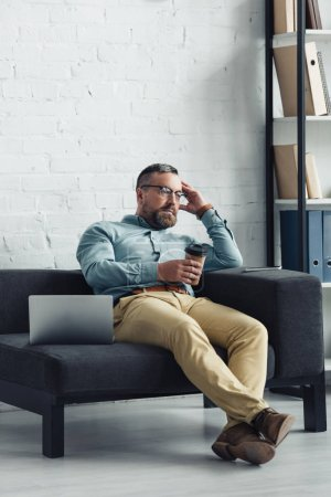 Photo pour Beau homme d'affaires retenant la tasse de papier et regardant loin dans le bureau - image libre de droit