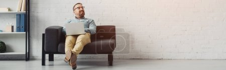 Photo for Panoramic shot of handsome businessman in shirt holding laptop and looking away - Royalty Free Image