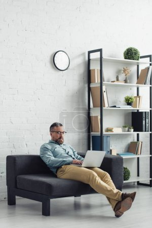Photo for Handsome businessman in shirt and glasses using laptop in office - Royalty Free Image