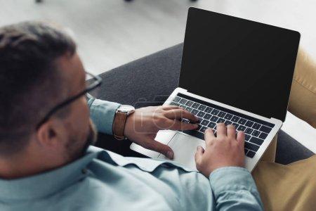 Photo pour Vue raccourcie de l'homme d'affaires dans la chemise et les glaces utilisant l'ordinateur portatif dans le bureau - image libre de droit