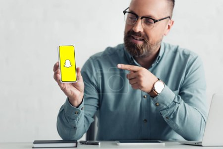 Photo pour Kiev, Ukraine - 27 août 2019: beau homme d'affaires en chemise pointant du doigt le smartphone avec le logo Snapchat - image libre de droit