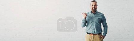 Photo pour Tir panoramique de l'homme d'affaires beau dans la chemise affichant le pouce vers le haut et regardant l'appareil-photo - image libre de droit
