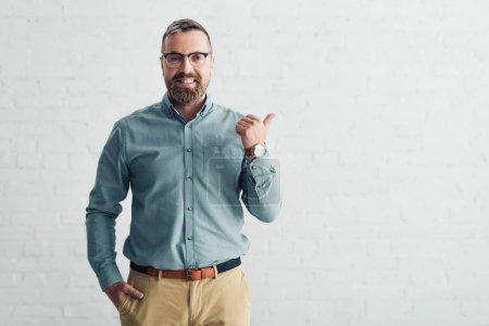 Photo pour Homme d'affaires beau dans la chemise affichant le pouce vers le haut et regardant l'appareil-photo - image libre de droit