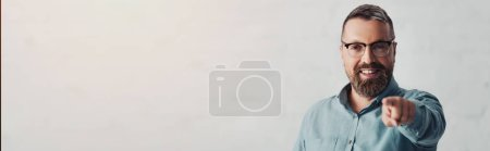 Photo for Panoramic shot of handsome businessman in shirt pointing with finger and looking at camera - Royalty Free Image