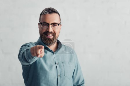 Photo for Handsome businessman in shirt pointing with finger and looking at camera - Royalty Free Image