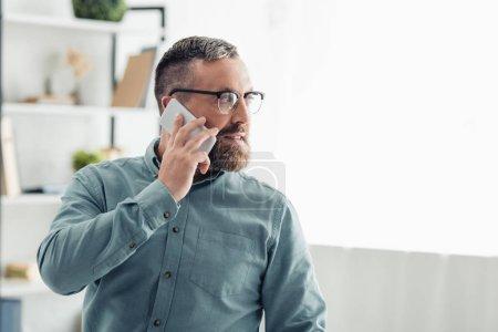 Photo pour Bel homme d'affaires dans la chemise parlant sur le smartphone et regardant loin - image libre de droit