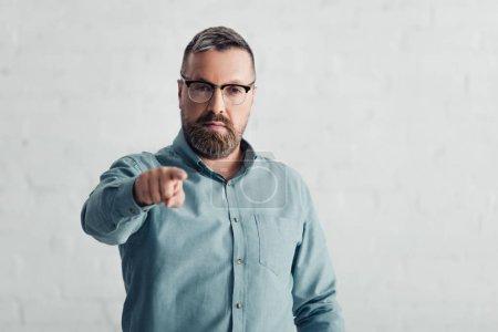 Photo pour Homme d'affaires beau dans la chemise pointant avec le doigt et regardant l'appareil-photo - image libre de droit