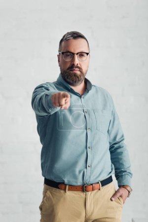 Photo pour Bel homme d'affaires en chemise pointant du doigt et regardant la caméra - image libre de droit
