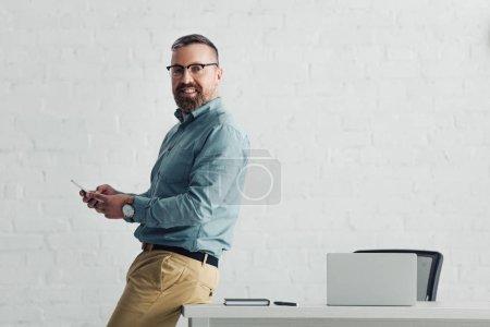 Photo pour Homme d'affaires beau dans le smartphone de fixation de chemise et regardant l'appareil-photo - image libre de droit