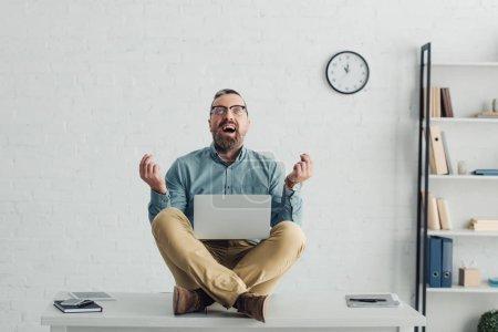 hombre de negocios guapo en camisa y gafas sentado en la mesa y la celebración de ordenador portátil