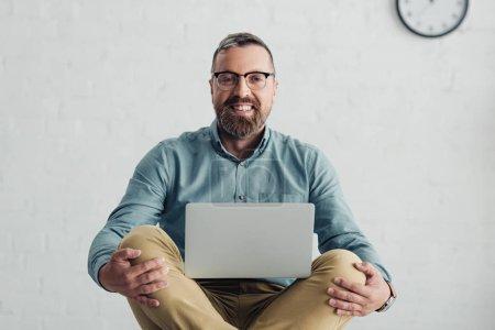 Photo pour Bel homme d'affaires en chemise et lunettes souriant et tenant ordinateur portable - image libre de droit