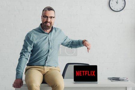 Photo pour Kiev, Ukraine - 27 août 2019: beau homme d'affaires en chemise pointant du doigt un ordinateur portable avec le logo netflix - image libre de droit
