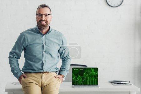 schöner Geschäftsmann sitzt am Tisch in der Nähe von Laptop mit Online-Handel-Website