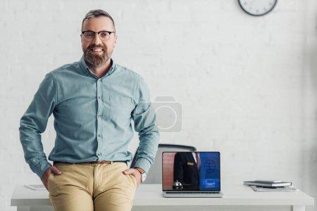 Photo pour Bel homme d'affaires assis sur la table près d'un ordinateur portable avec site de réservation - image libre de droit